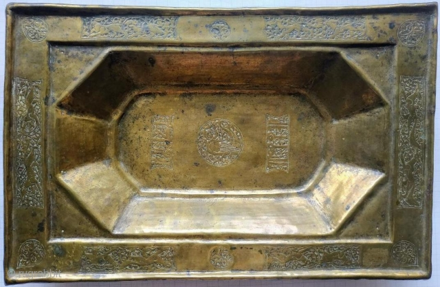 Tray, of rectangular form raised upon a lip, with a depressed eight-petalled design, decorated with arabesque and harpy panel and two panels with kufic script in the centre of the well, on  ...