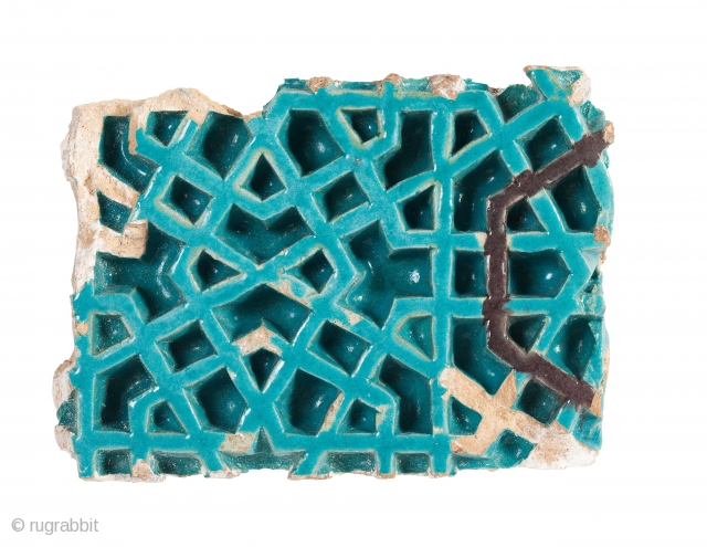 Timurid tile fragment, of rectangular form, decorated with a deeply incised geometric design, painted with turquoise and manganese glazes
