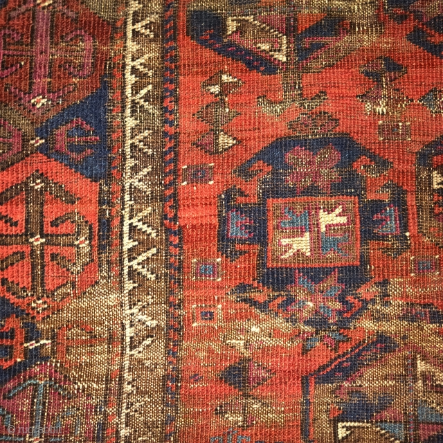 Worn and whipped rare red-ground Timuri type Baluch rug with a Saryk border. Madder red ground with cochineal highlights. Squarish shape.