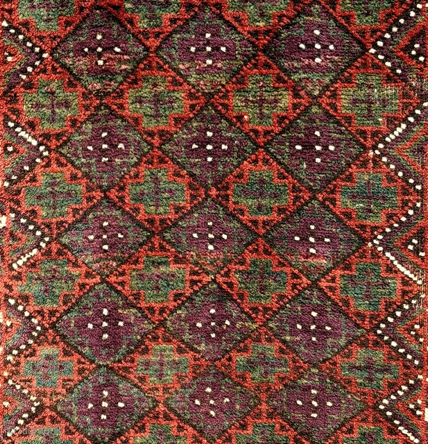 Antique Baluch balisht. Unusual palette, striking aubergine against a jade green and rust madder red. Fragmented ends and dense shimmering pile. A familiar design rendered with unusual minimalism and a distinctive array  ...