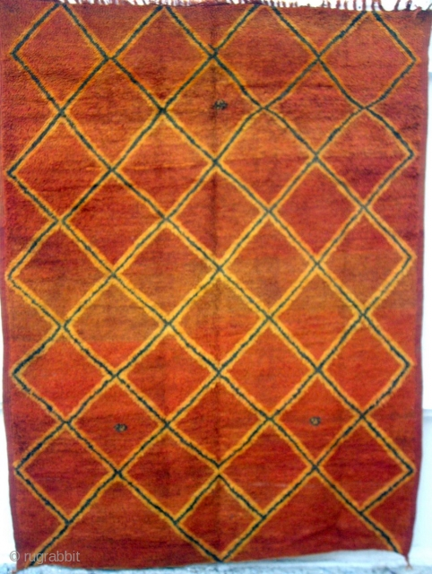 MOROCCAN RUG. This very old piece is from Rehamna which lies in the Haouz district, west of Marrakech. It has woollen warps and wefts and the mellow madder field has lattice designs  ...