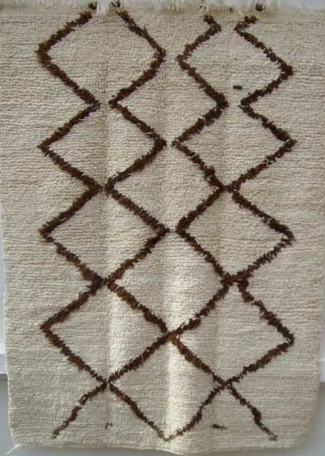 MOROCCAN HIGH ATLAS BERBER RUG. An unusual example where the pile has been woven with looped knots. The wools are soft and lustrous and the design is of dark brown undyed wool.  ...
