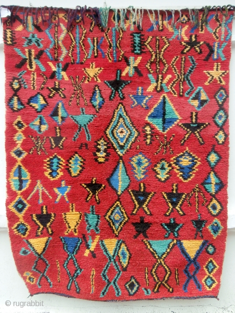 MOROCCAN BERBER HIGH ATLAS RUG A bright, colourful rug with a random scattering of Berber designs and motifs throughout the field. The colours are a deliberate contrast to the endless browns and  ...