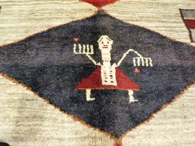 A very thick gabbeh, woven mainly with undyed soft wool. The central large figure has some triangular hankerchieves, so she might be dancing one of the traditional Qashqai dances. Her hands are  ...