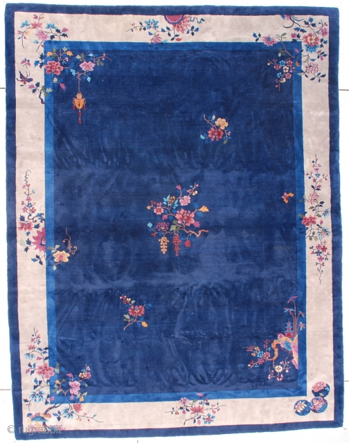 """This circa 1920 Art Deco Chinese Oriental Rug measures 9'0"""" X 11'9"""" (274 x 362 cm). It has a navy blue field containing a floral motif consisting of a rockery coming from  ..."""