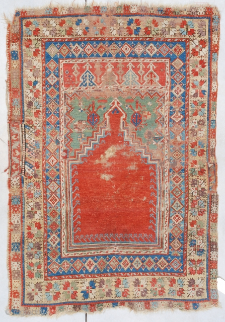 """#7464 Mudjur  This probably 18th century, possibly older Mudjur (Mucur) measures 3'9"""" X 5'3"""" (118 x 161 cm). This little prayer rug displays beautiful colors. The tomato red step prayer field outlined in  ..."""