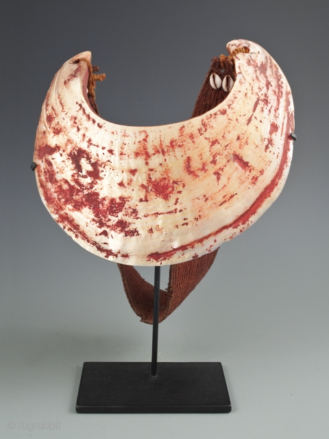 """Kina Shell Pectoral, Western Highlands, Papua New Guinea. Pearl shell, natural fibers, cowrie shells, natural pigment. 9"""" high by 8.5"""" wide, strap is 19.5"""" long. Early to mid-20th century. Ex Robin Lail."""