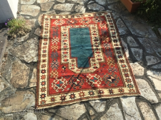 Sweet little kazak prayer rug dated 1902 or 3. Good condition. Simple and effective design. Good weave. 58 by 38 inches. Small area of repile on bottom left of the rug.