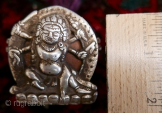 18th c. Tibetan Buddhist Silver Bhairava 'Gau' depicting Bhairava(Mahakala),  a fierce deity protector of Buddhist dharma;  copper backing,  efficacious for contact with the bare skin of the traveling lama;  ...