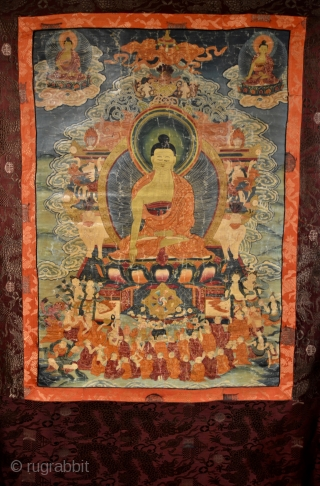 18th Century Thangka Depicting Shakyamuni Buddha, A stunning Tibetan thangka with Shakyamuni Buddha seated atop a lotus throne with hands in bhumisparsa mudra, surrounded by intricate narrative scenes with very fine details,  ...