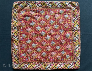 A fine antique Indian silk embroidered hanging from Gujarat (turned into a functional pillow). It dates around 1900  and is a really fine work of textile art. The red field is  ...