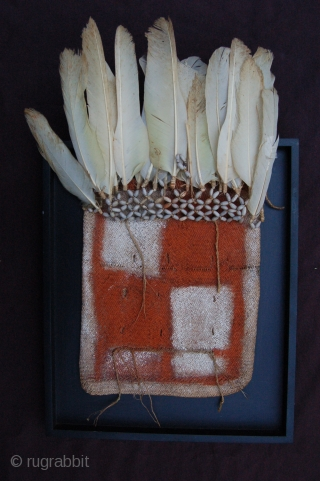 """Ethnographic Asmat tribe plant fibre bag with plant seed """"beads"""" and feather decoration 21 x 26 cm (8"""" x 10"""") Papua New Guinea. Condition: very good, mounted on a frame."""