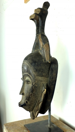 Baoulé,  The BAOULE masks are known in African art for the smoothness of their features, protruding mouth, half closed eyes.  The mask is topped with a headdress decorated with towering braids.  The  ...