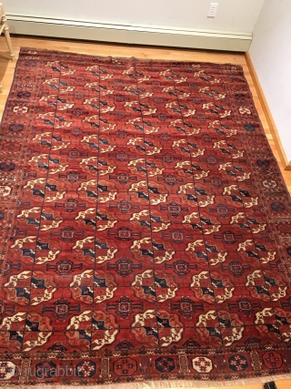 Tekke Main Carpet.  1st Half 19th Century.   Spacious red-purple field displays large rounded Tekke guls and secondary Gurbaghe guls connected by a fine line.  Cruciform star end borders  ...