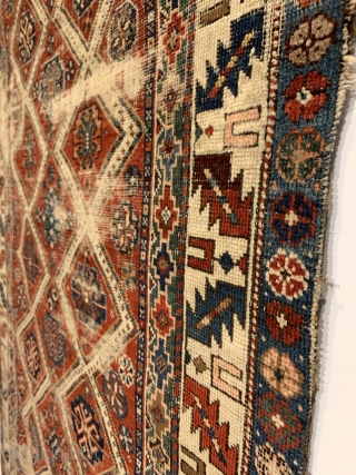 Antique Caucasian Small Rug. Circa Early. Two columns of ivory diamond lattice with alternating rows of gols. Leaf and wine glass border. Remnants of embroidered macrame ends on top. Original condition with  ...