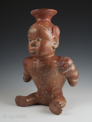 """Seated dwarf vessel, Colima, West Mexico. Earthenware, slip, 11"""" (28 cm) high. 100 BC - 250 AD.  A reddish-brown painted earthenware seated dwarf with out-turned legs and bulging muscular arms. He wears a  ..."""